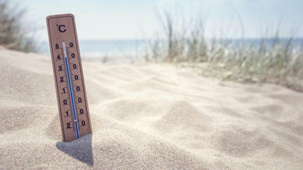 Termômetro fincado em areia de praia marca temperatura alta