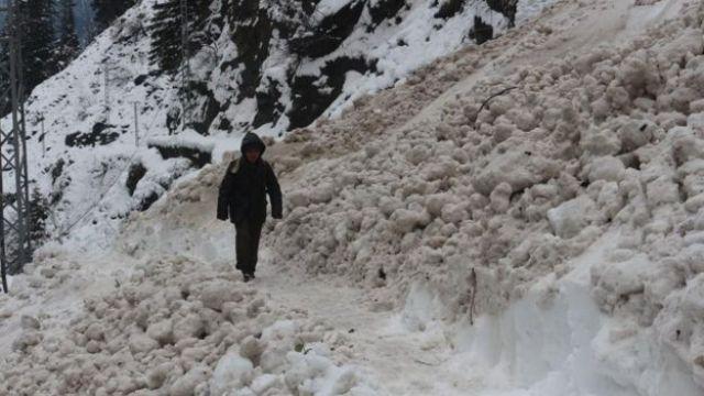 Boy walks in snow in Neelum valley - roads are cut off