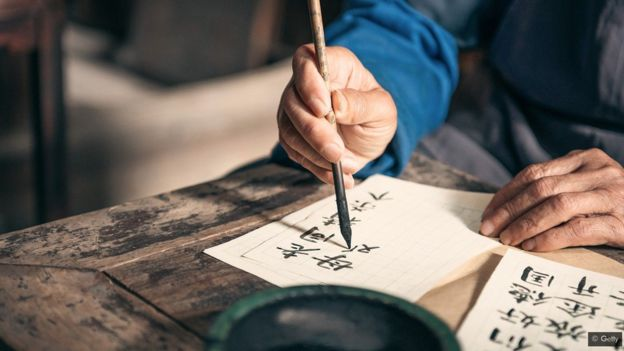 An old person uses traditional tools of ink and brush to write Asian calligraphy