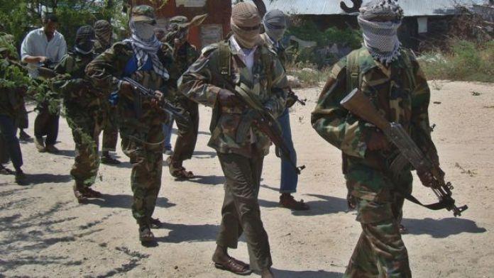 Militants in al-Shabab walk down a street in Mogadishu, Somalia