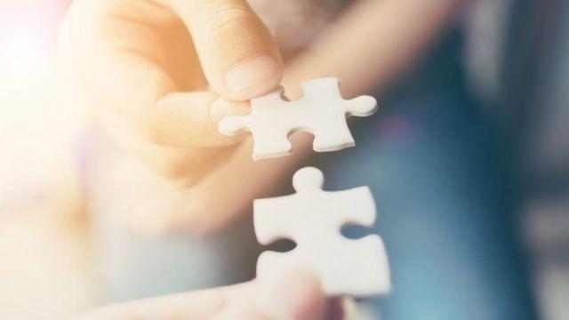 Mãos de uma criança e um adulto, ambas segurando uma peça de quebra-cabeça