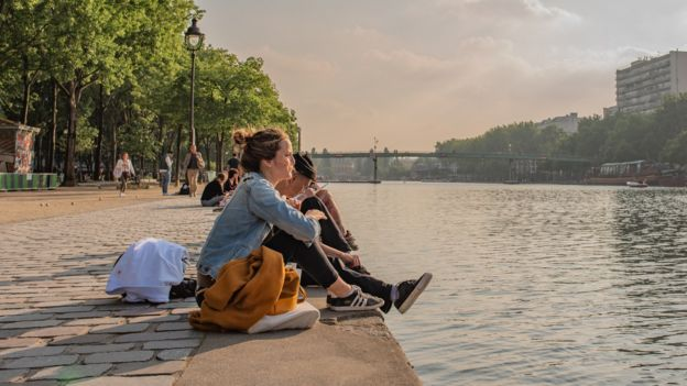Women sitting by the canal in Paris