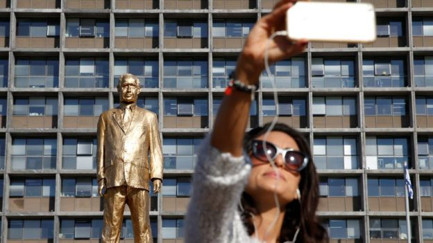 A woman takes a selfie in front of the golden Netanyahu statue