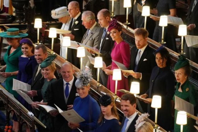 """Queen Elizabeth II, the Duke of Edinburgh, the Prince of Wales, the Duke of Cambridge, the Duchess of Cambridge, the Duke of Sussex, the Duchess of Sussex and the Princess Royal, (left to right front row) Sarah Ferguson, Princess Beatrice, Peter Phillips, Autumn Phillips, Mike Tindall, Zara Tindall, Lady Louise Mountbatten-Windsor and Crown Prince Pavlos of Greece at the wedding of Princess Eugenie to Jack Brooksbank at St George""""s Chapel in Windsor Castle"""