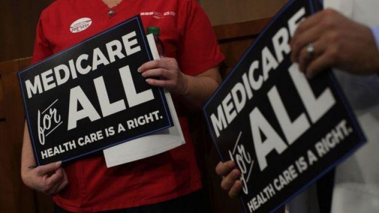 Pessoas seguram cartazes pedindo a criação do sistema de saúde universal Medicare for all