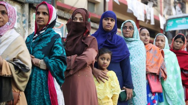 Female voters with children stand in a queue at a voting centre in Dhaka