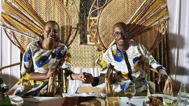 Arlene Agneroh and Jean-Felix Mwema Ngandu hold hands and smile as they sit side by side on throne-like chairs