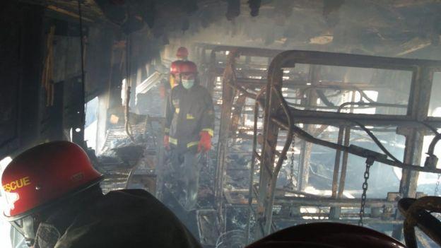 Pakistan firemen board the train that was set alight on 31 October