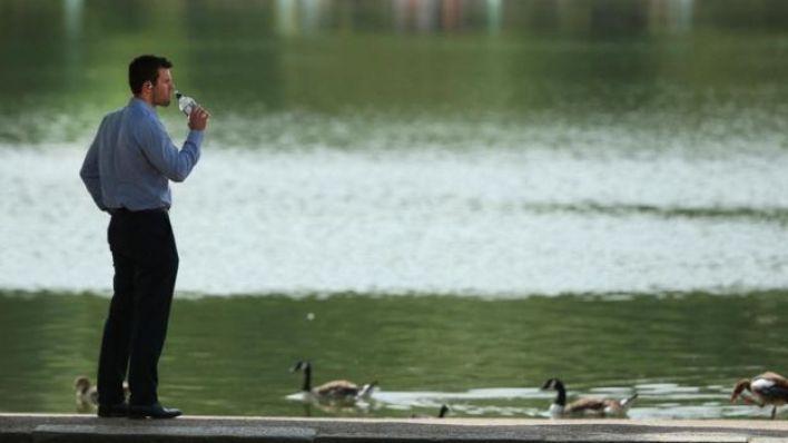 شاب يحمل زجاجة مياه ويقف أمام مجرى مائي
