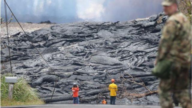 Militar e outras duas pessoas aparecem na imagem próximos à lava emitida pelo vulcão Kilauea