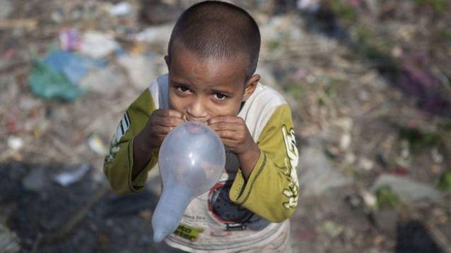 Criança usando camisinha como balão de ar, no meio do lixo