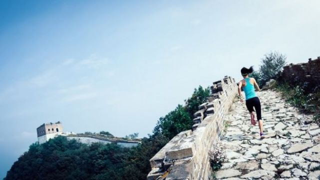 Female athlete cross country running on the Chinese great wall.