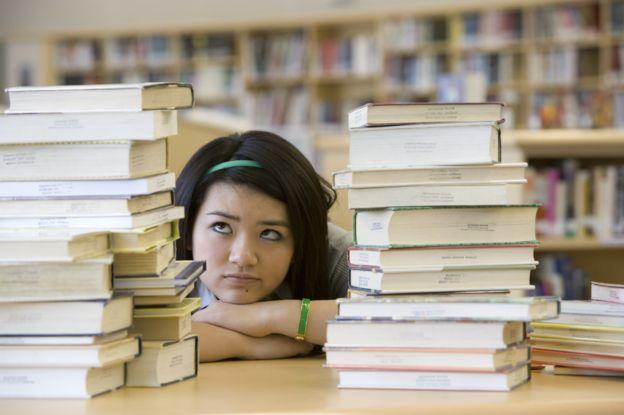 Jovem com pilha de livros