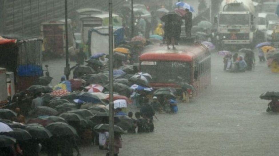 Pessoas sobem em ônibus em área alagada