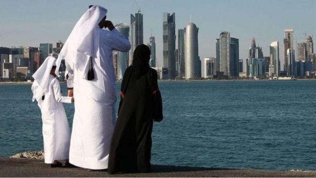 Um homem e duas crianças em trajes tradicionais olham para uma cidade no Golfo Pérsico