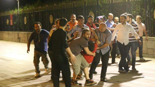 People carry an injured man in Ankara, Turkey, on 16 July 2016