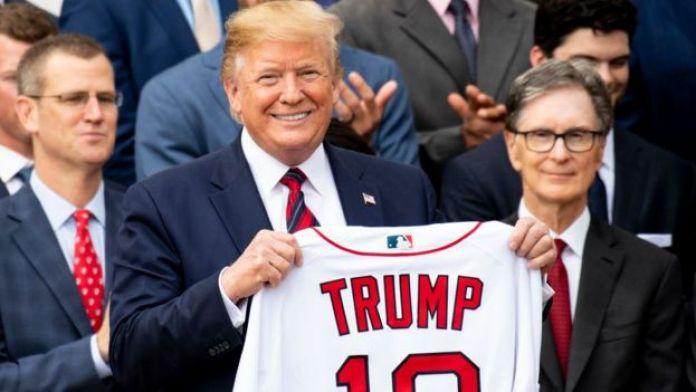 Donald Trump segurando uma camisa com o próprio nome
