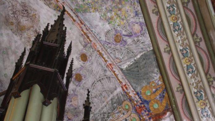 Argamassa sobre pinturas de Gino Catani no teto da igreja. Em primeiro plano, o que sobrou do órgão alemão do coro