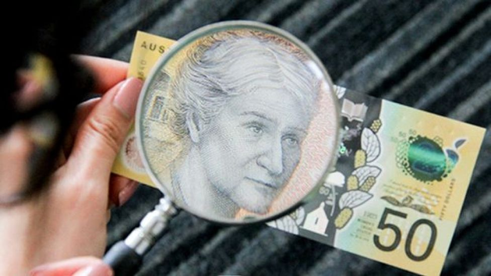 El billete de 50 dólares australianos con una lupa.