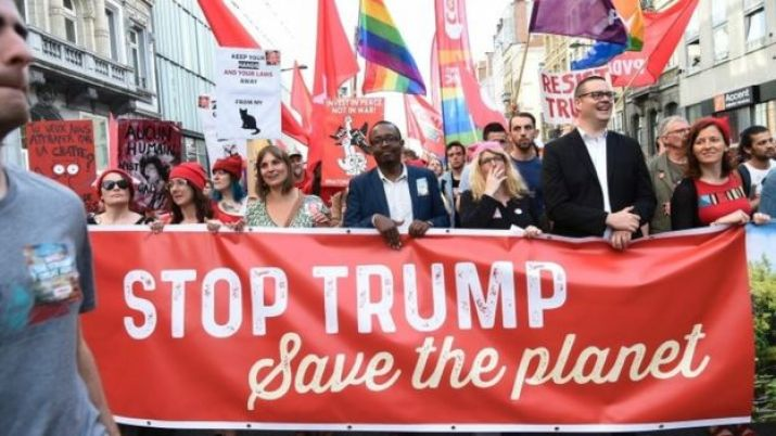 Protesters hold a banner as they take part in a demonstration against the US president in Brussels on May 24, 2017