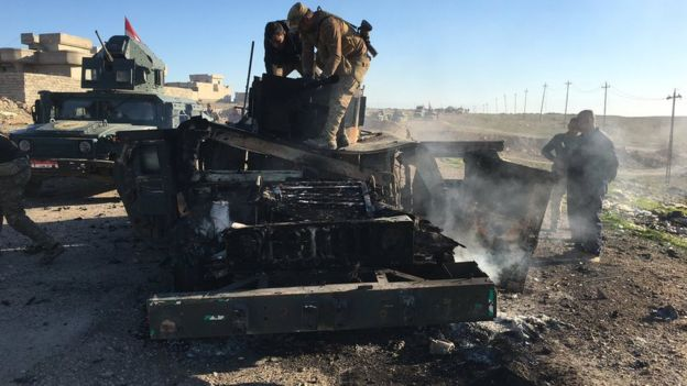 An army vehicle with its front ruined an smoking from an explosion is seen at the front of a convoy, as soldiers examine the damage.