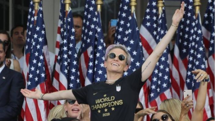 Rapinoe poses in front of flags