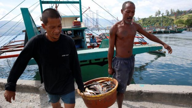 Fishermen, who has just returned from fishing in disputed Scarborough shoal, unload fish from a boat in Subic, Zambales in the Philippines