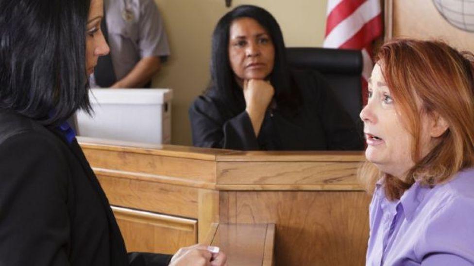 Un juge regarde une femme témoigner devant le tribunal.