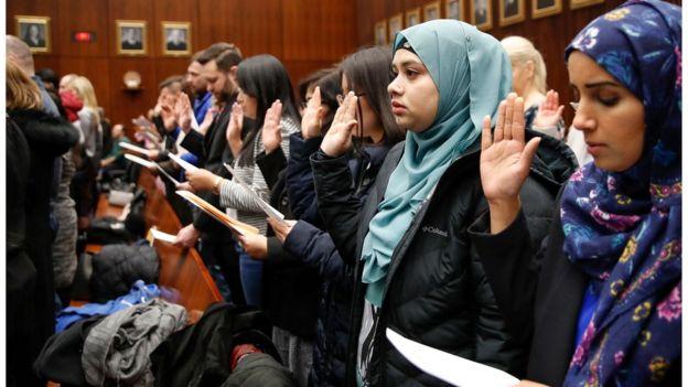 Personas prestan juramento para convertirse en ciudadanos estadounidenses.
