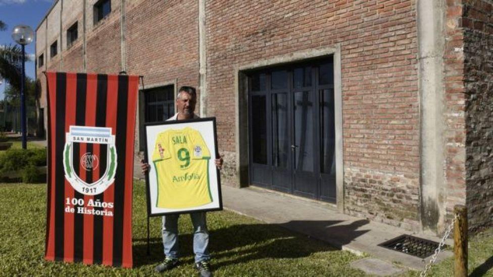 San Martin de Progreso president Daniel Ribero holding a framed shirt