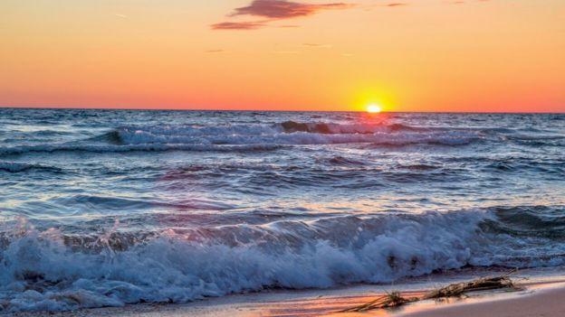 Imagem mostra o mar, com o sol se pondo, ao fundo
