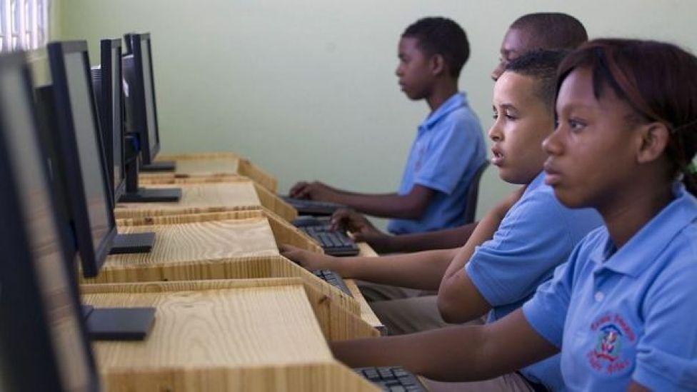 Crianças estudando em computadores