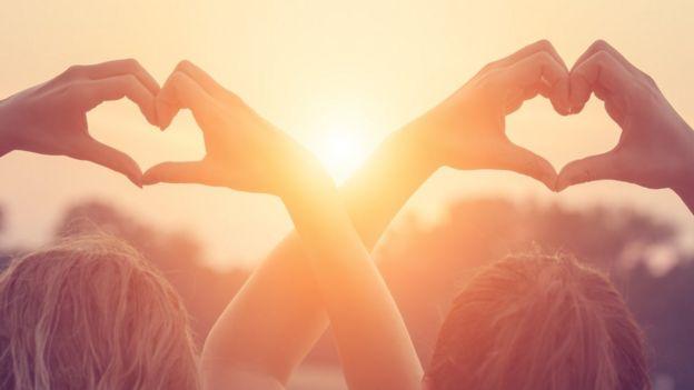 Duas pessoas fazem coração com as mãos
