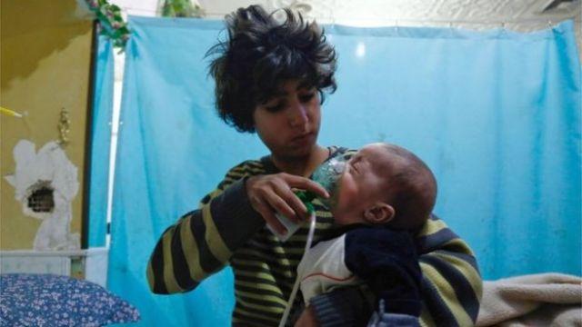 Garoto coloca máscara de oxigênio sobre bebê em hospital itinerante em Douma, Síria