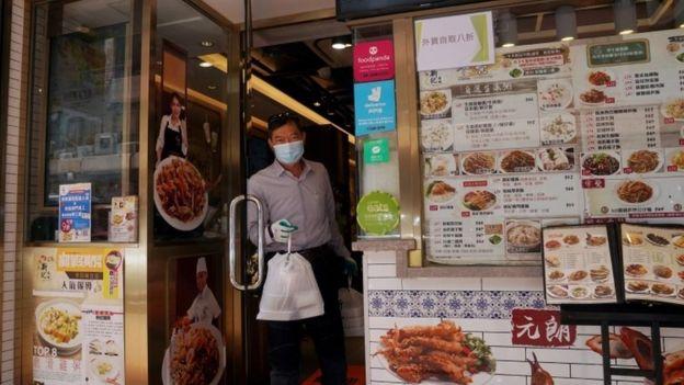 Un homme reçoit un plat à emporter d'un restaurant de Hong Kong