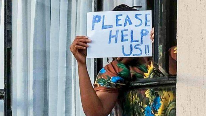 """Une personne en quarantaine au Kenya brandit un panneau """"Aidez-nous"""" - avril 2020"""