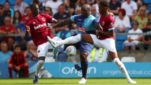 Adebayo Akinfenwa of Wycombe Wanderers battles for the ball with Reece Oxford (R) and Pedro Obiang of West Ham