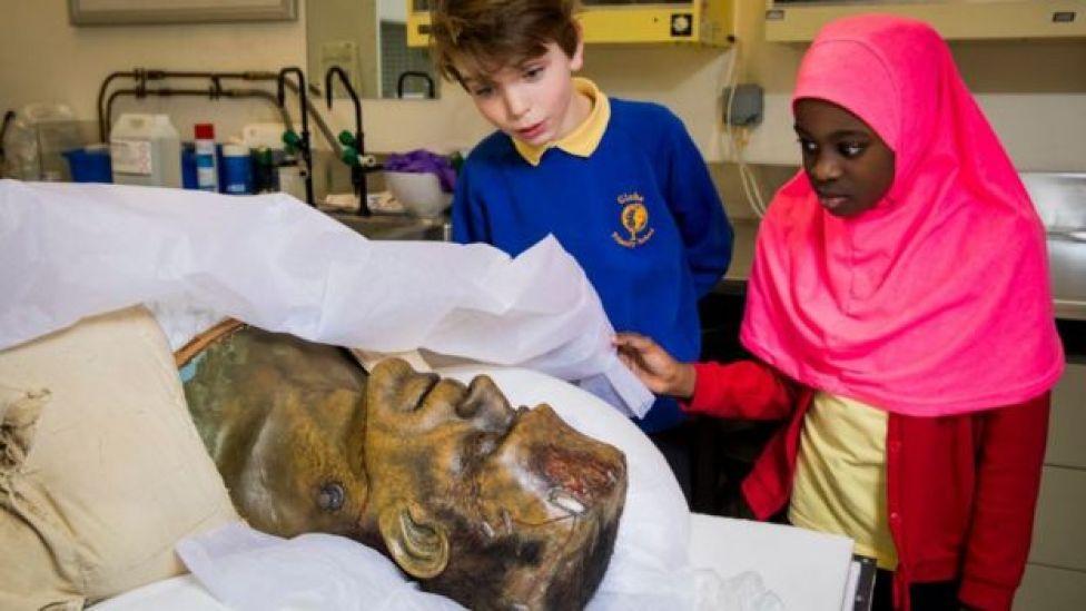 Enfants examinant une tête de Frankenstein