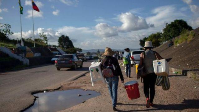 Imigrantes caminham carregando malas e bancos no acostamento de uma estrada na fronteira entre Brasil e Venezuela