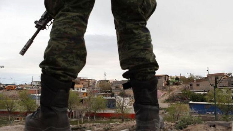Um policial militar segura arma no México