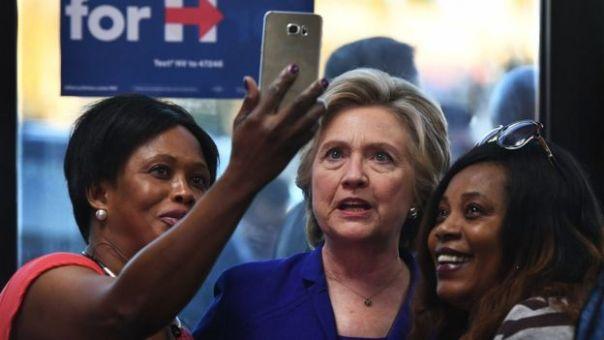 Hillary Clinton tomándose una selfie con dos votantes.