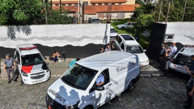 Carros da polícia militar e de funerárias em frente à escola Raul Brasil