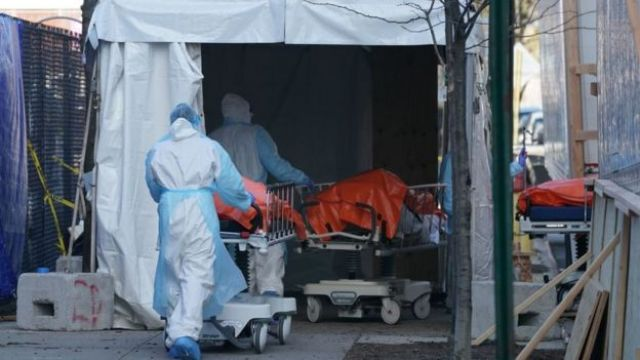 Bodies are loaded onto a refrigerated lorry which is serving as a makeshift morgue.