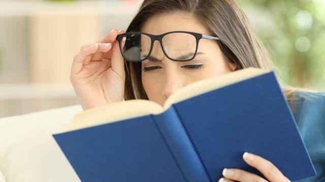 Mulher de óculos com dificuldade para ler livro