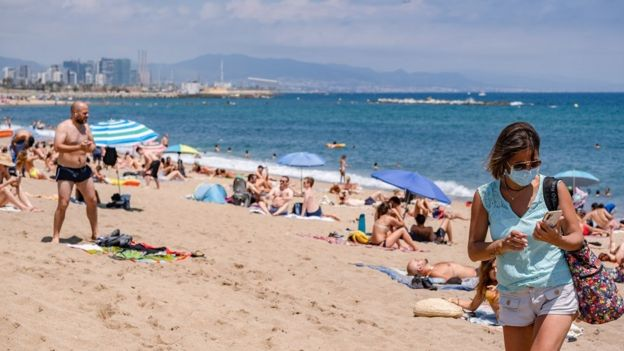 A woman wearing a face mask is seen leaving the beach. The city of Barcelona faces new outbreaks of coronavirus cases with new mobility restrictions and recommendations to avoid travelling outside the city.