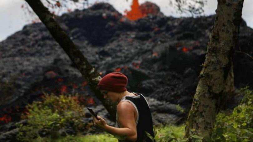 Imagem mostra homem usando o celular com vulcão em erupção, ao fundo