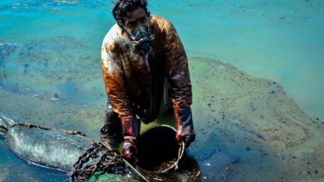 Le 8 juin, un homme récupère de l'huile provenant du navire MV Wakashio.