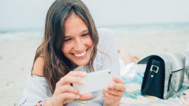 Mujer sonriendo al mirar su teléfono
