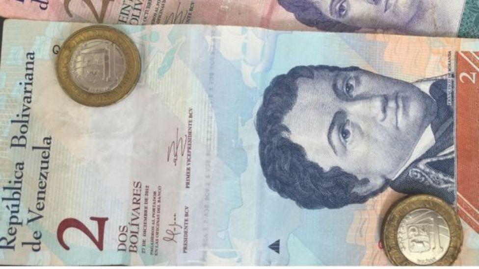 Un billete de 2 bolívares y dos monedas de uno.