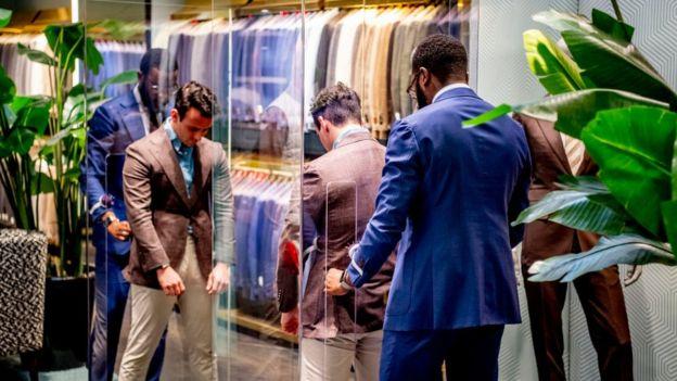 بائع في محل ملابس في هولندا يساعد زبونا في ارتداء سترة عبر فتحات في فاصل زجاجي